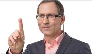 Bild på man med OrCam glasögon håller upp fingret framför sig.