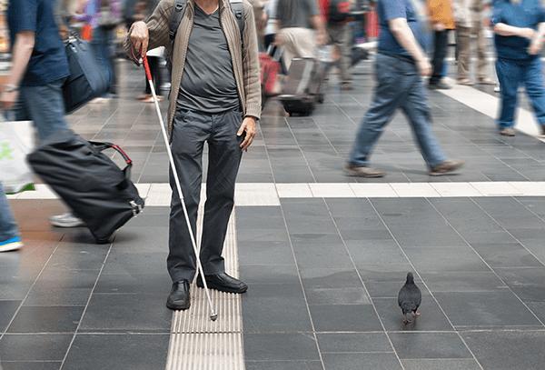 Man med vit käpp på gata